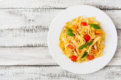 Fettuccine pasta in tomato sauce with chicken, tomatoes decorated with basil Stock Photos