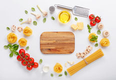 Fettuccine and spaghetti with ingredients for cooking pasta. On a white background with blank of wooden kitchen board, top view. Flat lay royalty free stock image