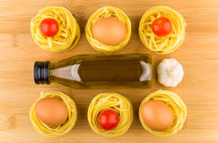 Fettuccine with tomatoes, eggs, garlic and olive oil in bottle. On wooden board, top view Stock Photo