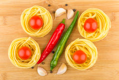Fettuccine with tomatoes, garlic and chili peppers on wooden boa Royalty Free Stock Photo