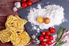 Fettuccinedeg, ägg, mjöl, vitlök, körsbärsröd tomat och rosmarin Royaltyfria Foton