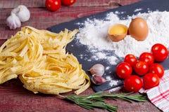 Fettuccinedeg, ägg, mjöl, vitlök, körsbärsröd tomat och rosmarin Arkivbilder