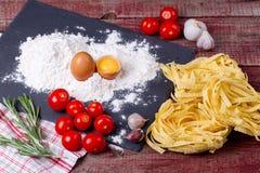 Fettuccinedeg, ägg, mjöl, vitlök, körsbärsröd tomat och rosmarin Royaltyfri Bild