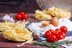 Fettuccinedeg, ägg, mjöl, vitlök, körsbärsröd tomat och rosmarin Arkivbild