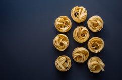 Fettuccini italiano de las pastas en un fondo negro imagen de archivo
