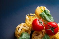 Fettuccini italiano de las pastas en un fondo negro fotografía de archivo