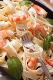 Fettuccini pasta in cream sauce with shrimp macro. Vertical Stock Photo