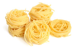 Fettuccini pasta nests. On a white background stock photography