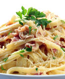 Fettucine Carbonara. In a white bowl, garnished with parmesan and parsley.  Delicious creamy sauce Royalty Free Stock Photography