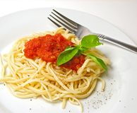 Fettucine pasta. Plate of fettucini with tomato sausse and pepper royalty free stock image
