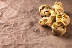 Fettucine pasta på bakgrund för brunt papper Fotografering för Bildbyråer