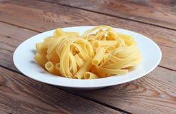 Fettucini cru d'un plat blanc Photos libres de droits