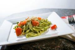 Fettucini pasta with pesto sauce. And fresh tomatoes Royalty Free Stock Photography