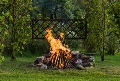 Feu dans le jardin avec le grillage prêt pour un BBQ Photos stock
