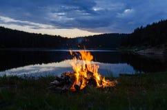 Feu de camp après coucher du soleil dans les montagnes à côté d'un lac images libres de droits