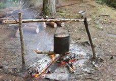 Feu de camp avec la chaudière dans la forêt Photographie stock