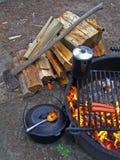 Feu de camp de pique-nique, bois, hache, bac de café, hot dogs, cuillère, bouilloire, et grille Photos libres de droits