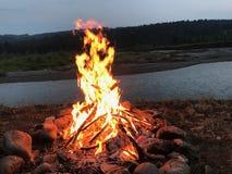 Feu de camp devant la rivière Photographie stock libre de droits