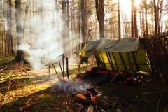 Feu de camp fumeux devant le maigre de bushcraft au camp Images libres de droits