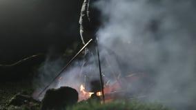Feu de camp la nuit Équipez ajouter les bois dans le feu et corriger des charbons banque de vidéos