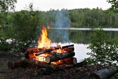 Feu de camp par le lac photo stock