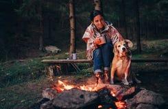 Feu de camp proche chaud de femme et de chien dans la forêt Photos stock