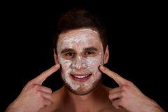 Feuchtigkeitscreme des Mannes mit Sahne auf seinem Gesicht Lizenzfreies Stockfoto