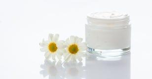 Feuchtigkeitscreme und Kamille auf weißem Hintergrund lizenzfreie stockfotos