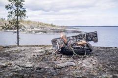 Feuer auf dem felsigen Ufer des Sees, auf einem Hintergrund von Himmel a Stockfoto