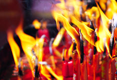 Feuer auf Kerzen nach dem buddhistischen Beten im Tempel Stockbilder