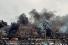 Feuer in einem industriellen Lager oder in einer Fabrik, viele Rauch und Flammen Stockfotografie