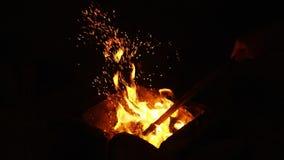 Feuer funkt, Dunkelheit am schwarzen Hintergrund weiter gehend, der von warm hell brennen kommt stock footage