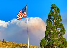 Feuer-Wolken-Wogen hinter US-Flagge lizenzfreies stockfoto