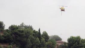 Feuerbekämpfender Hubschrauber lässt einen Wasser-Tropfen ein Haus schützen stock footage
