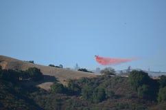 Feuerbekämpfendes Flugzeug-von der Luftc$fallen feuerverzögernd Lizenzfreies Stockfoto