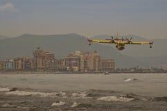 Feuerbekämpfendes Flugzeugfliegen über dem Meer auf dem Strand stockfoto