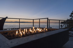 Feuergrube durch das Meer bei Sonnenuntergang Stockbild