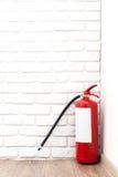 Feuerlöscher nahe weißer Wand Stockfotografie