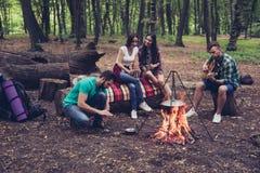 Feuern Sie Platz, vier nette ruhige Touristen sitzen herum ab Stockfotografie