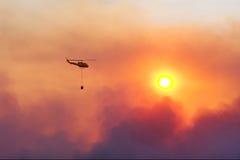 Feuerrettungshubschrauber, der Feuer gegen Sonnenuntergang Dämpfung ist Stockfotos