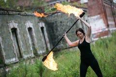 Feuershowmädchen mit Flammenfackeln Stockbilder