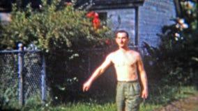 Feuerstein, Michigan 1965: Männer, die Hufeisen in der Schmutzgassenstraße hinter dem Haus spielen stock video
