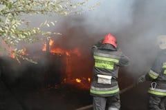 Feuerwehr in der Aktion während der brennenden Lager mit Plastikprodukten Lizenzfreie Stockfotografie