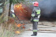 Feuerwehr in der Aktion während der brennenden Lager mit Plastikprodukten Stockfotos