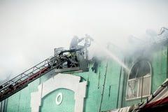 Feuerwehrmänner in Aktion Fighting, Feuer, im Rauche auslöschend Stockbilder