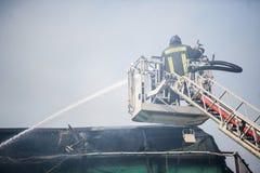 Feuerwehrmänner in Aktion Fighting, Feuer, im Rauche auslöschend Stockfotografie