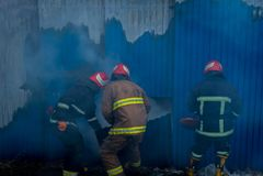 Feuerwehrmänner arbeiten an einem Feuer des Gebäudes unter Verwendung eines Metallschneider-Rettungswerkzeugs während eines Feuer Stockbild
