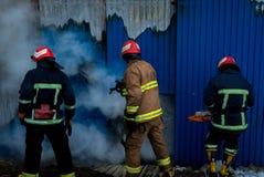 Feuerwehrmänner arbeiten an einem Feuer des Gebäudes unter Verwendung eines Metallschneider-Rettungswerkzeugs während eines Feuer Lizenzfreies Stockfoto