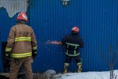 Feuerwehrmänner arbeiten an einem Feuer des Gebäudes unter Verwendung eines Metallschneider-Rettungswerkzeugs während eines Feuer Lizenzfreie Stockfotos