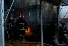 Feuerwehrmänner auf Feuer Zwei sprechendes Firemans, wenn Drittel das Feuer mit Wasser auslöscht Externer Markt brennt Stockbilder